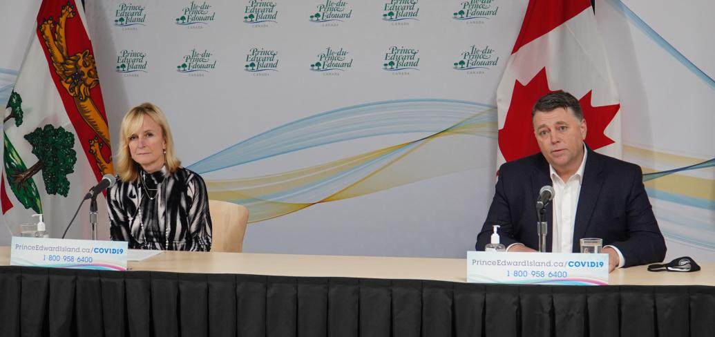 image of two people sitting behind a long table with flags behind them.