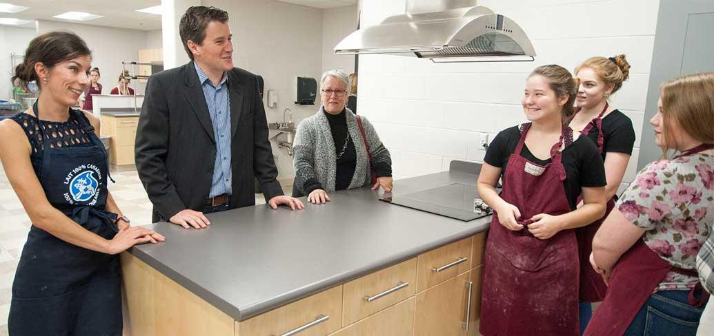 Photo shows ministers speaking with students in the newly renovated culinary arts kitchen.