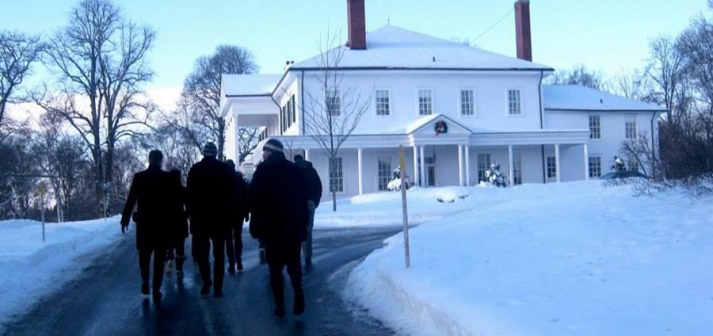 A group of people walk toward Government House.