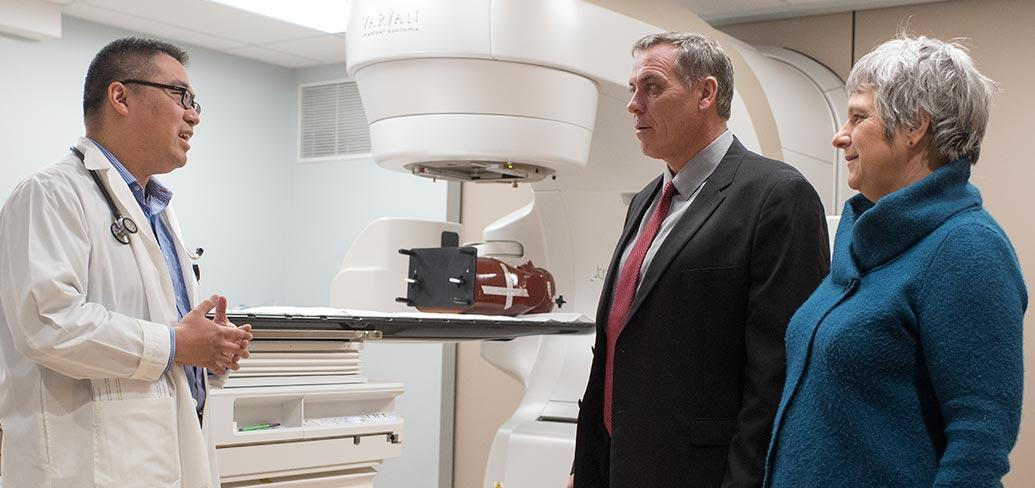 Three people stand beside the new $10 million state-of-the-art TrueBeam linear accelerator at the Queen Elizabeth Hospital