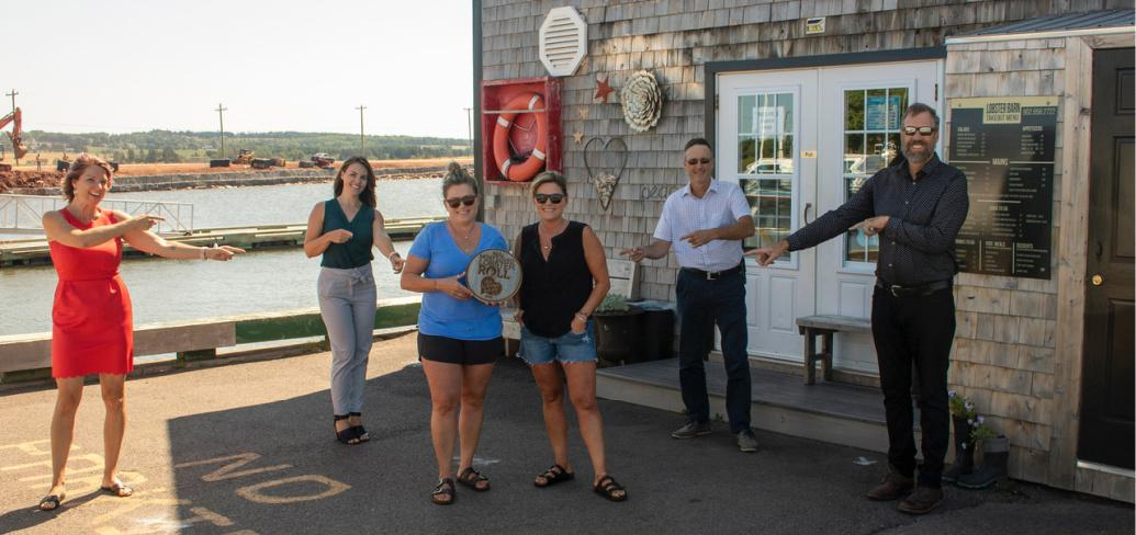 Staff from the Lobster Barn stand, along with others, outside their restaurant holding their winning plaque