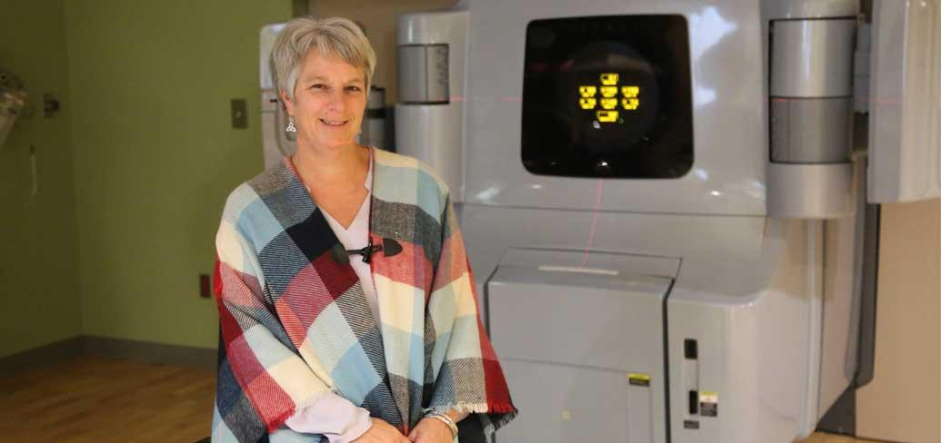 Dawn MacIsaac sits by one of the older Linear Accelerator's at the PEI Cancer Treatment Center