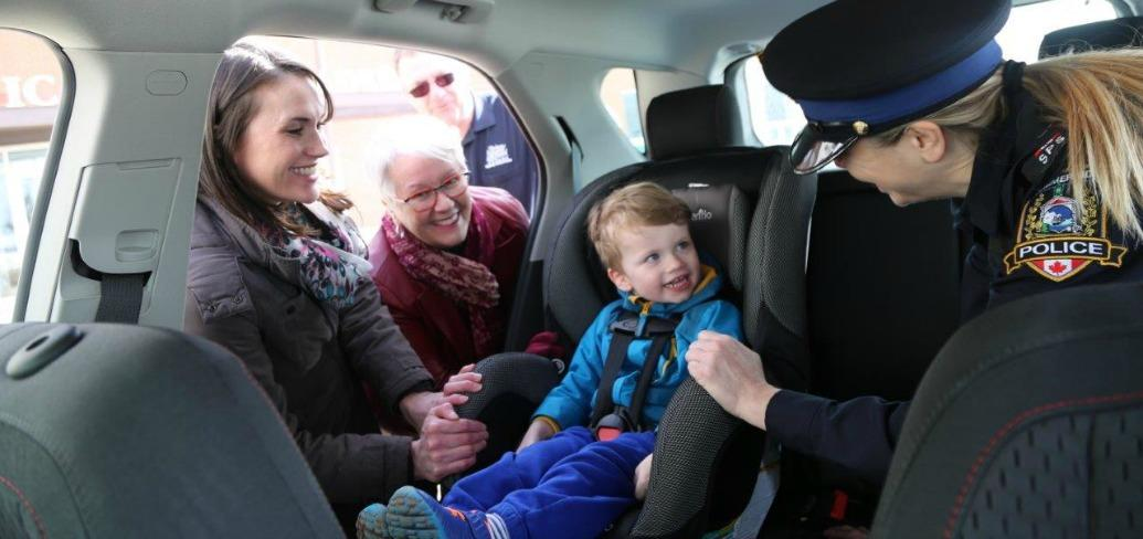Summerside mom and child get tips on car seat safety along with Minister Paula Biggar,  Summerside Police Cpl. Jennifer Driscoll and Highway Safety Officer Kevin Gillian