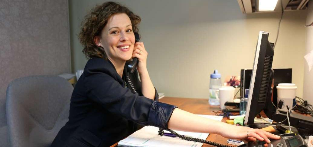 Mary Laura Coady speaks on her telephone while sitting at her desk