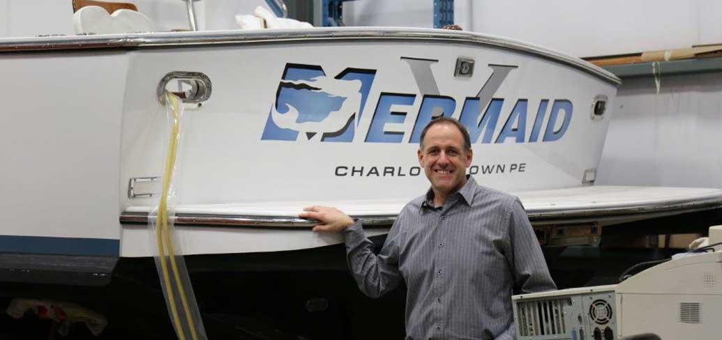 General Manager Ron Savidant stands in front of fishing vessel inside their Charlottetown Industrial Park site