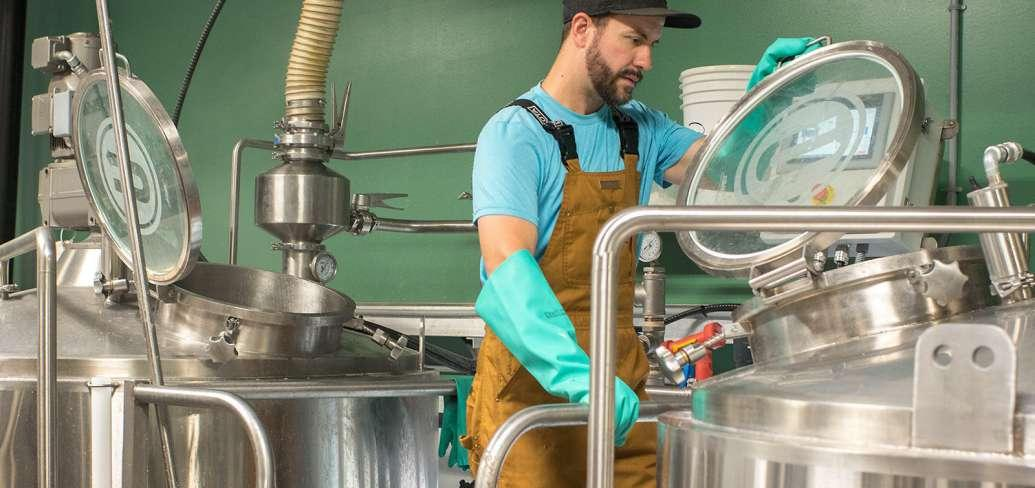 Brew master checks batch in DME kettle