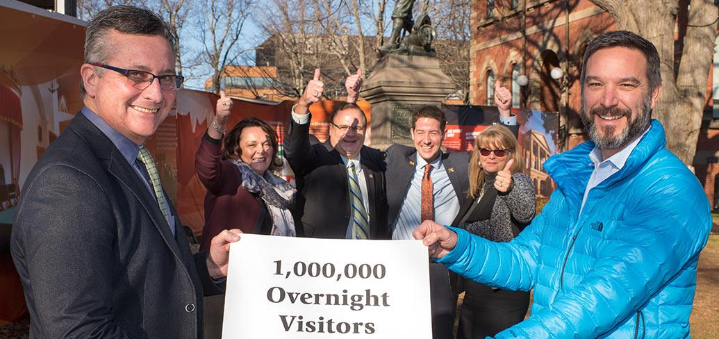 "Photo shows Minister MacDonald holding a sign with several other individuals that says ""one million overnight stays"""