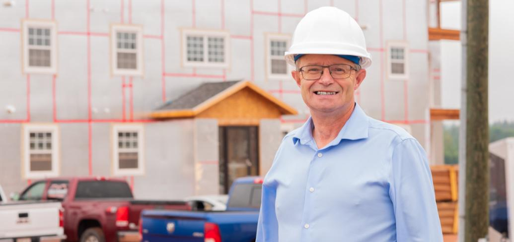 Man in a hard hat standing in front of a building under construction