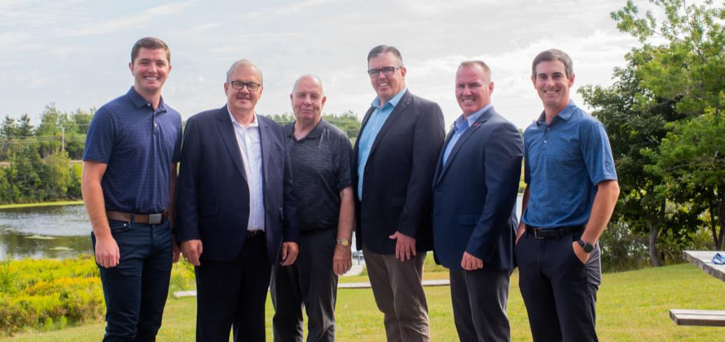 Six men stand on the bank of the Morell river following a federal provincial funding announcement