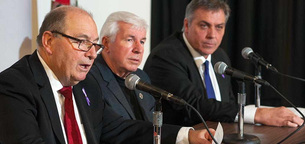 Photo shows three gentleman seated speaking into microphones