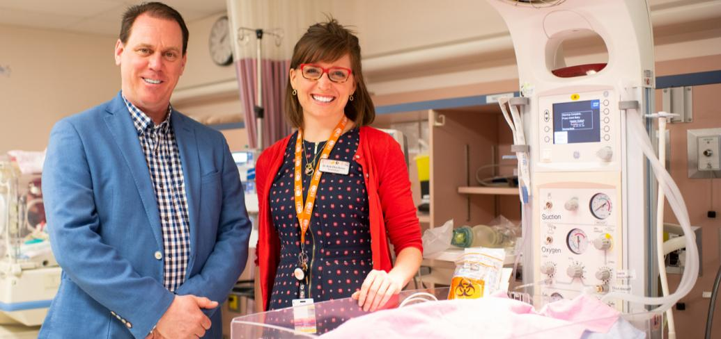 Two people standing beside some infant equipment in a hospital.
