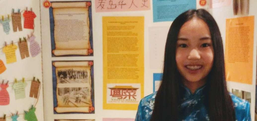 Olivia Lewis stands in front of her heritage display on 'L'immigration Chinoise au Canada' at the PEI Heritage Fair
