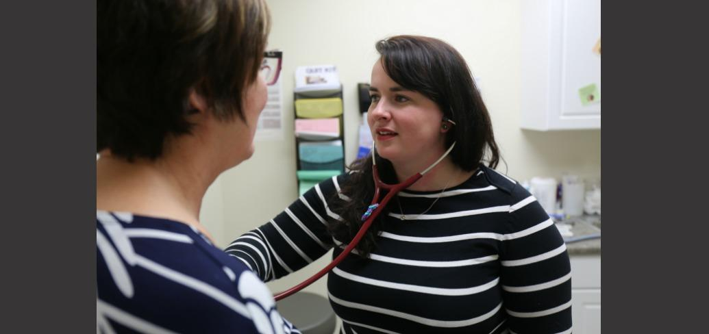 Nurse Practitioner Melinda Ells is shown with a patient.
