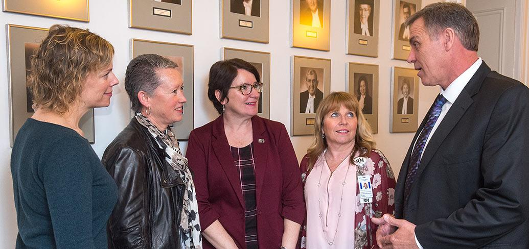 Nurses Cynthia Bryanton, Anita MacKenzie and Debbie Flood-Vickerson, as well as Director of Public Health Nursing and Child Development Jill Anne McDowall, speak with Minister Mitchell about nursing on PEI