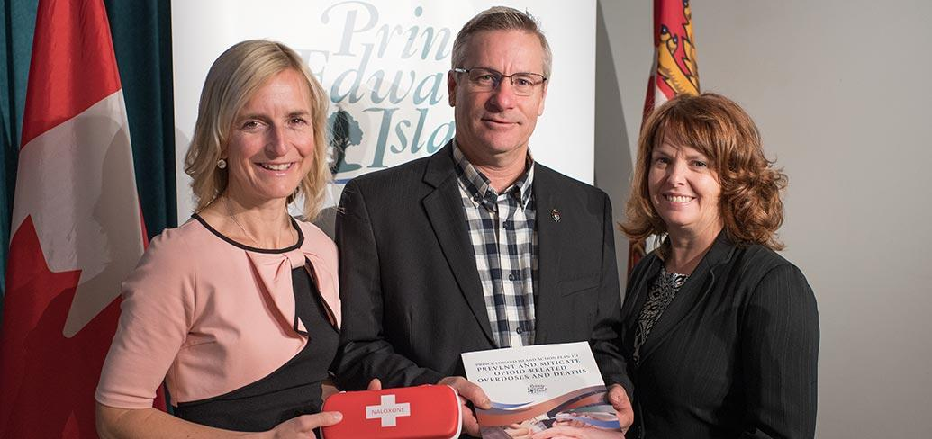Photo shows Dr. Heather Morrisson holding a Naxolone kit, Minister Robert Henderson holding the plan, and Karen MacDonald of Justice and Public Safety.