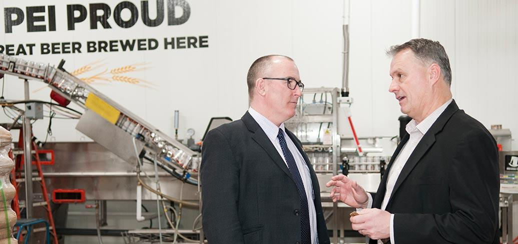 Two people speaking to each other while standing in front of brewing equipment