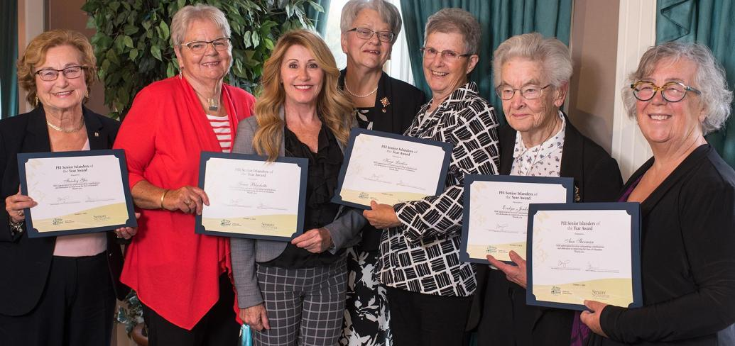 Seven women stand in a row, five of them holding certificates for Senior Islander of the Year