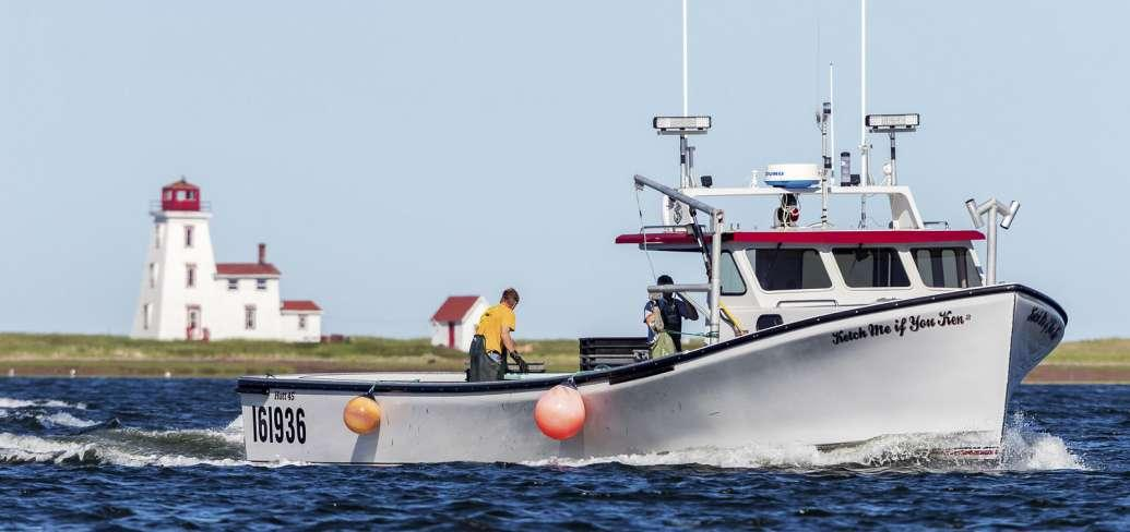 Fishing boat sails past Souris lighthouse