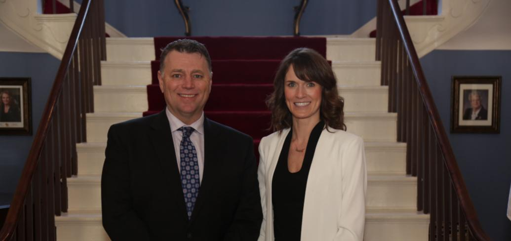 Premier King stands with Minister Jameson in front of the stairway in Government House
