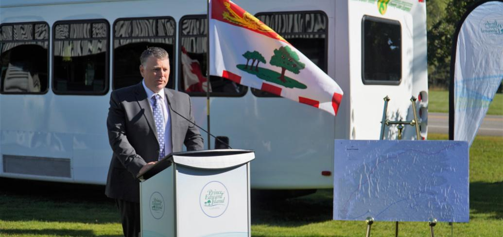 Person standing at podium with flag in background