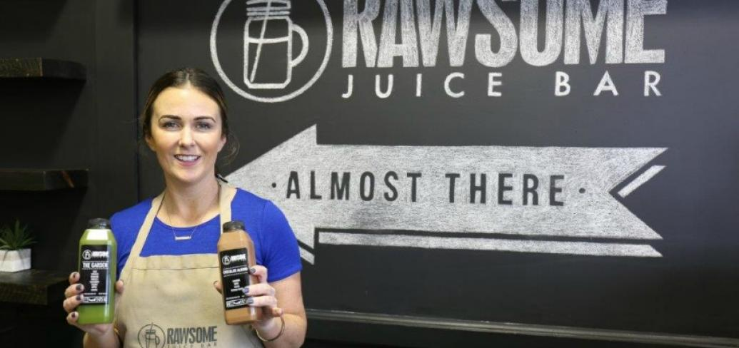 Suzanne Keough stands in front of the sign for her business, Rawsome Juice, holding jars of juices she's made.