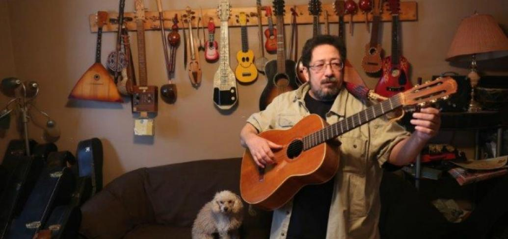 Scott Parsons is shown holding his guitar, in his home studio with guitars hanging on the wall
