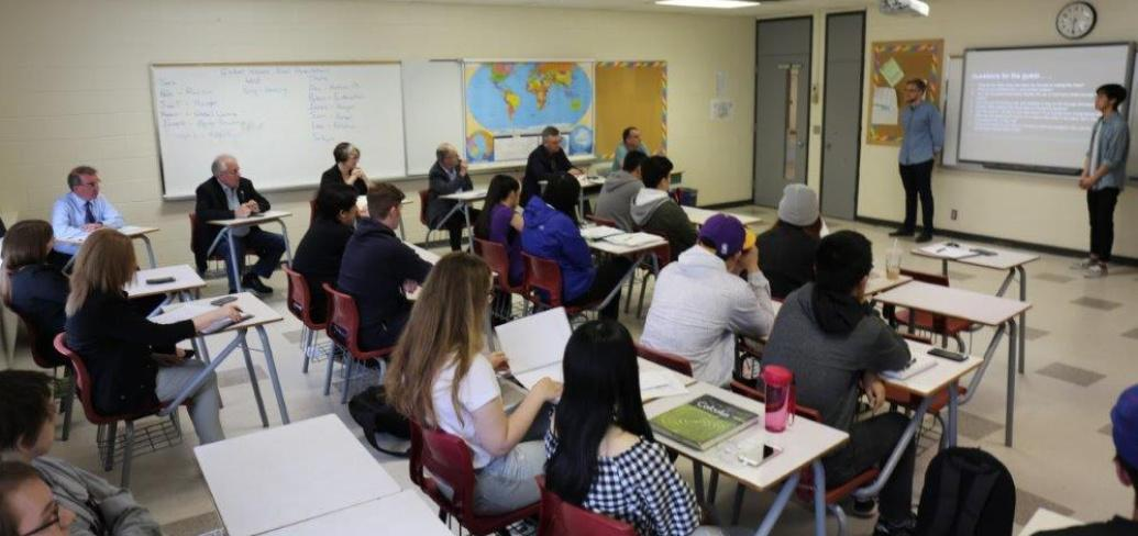 Grade 12 students Connor Crosby and Young Hao Yu stand making a presentation to their Global Issues class at Colonel Gray