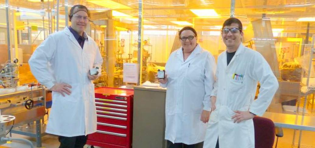 Group of three employees in lab coats display product