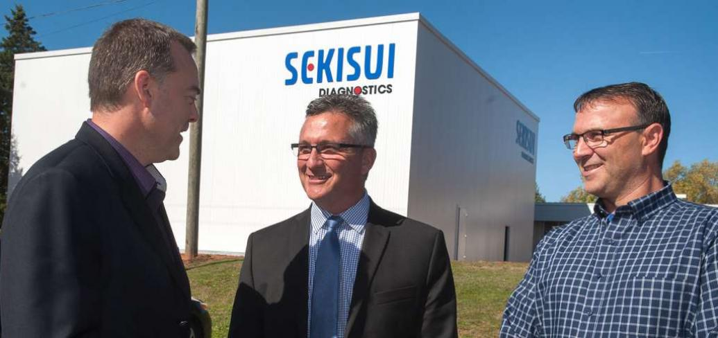 Minister Heath MacDonald and two men standing in from of Sekisui Diagnostics building
