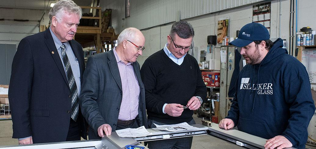 Photo shows four men examining a piece of glass