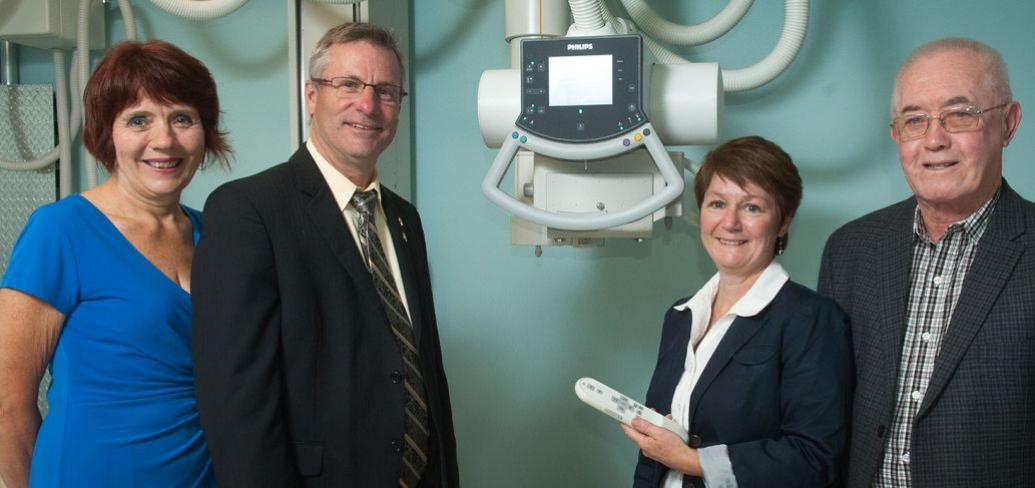 Minister of Health and Wellness, Robert Henderson and three people stand n front of a diagnostic imaging machine.