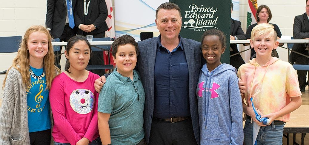 Premier King and some children standing shoulder to shoulder in front of some tables