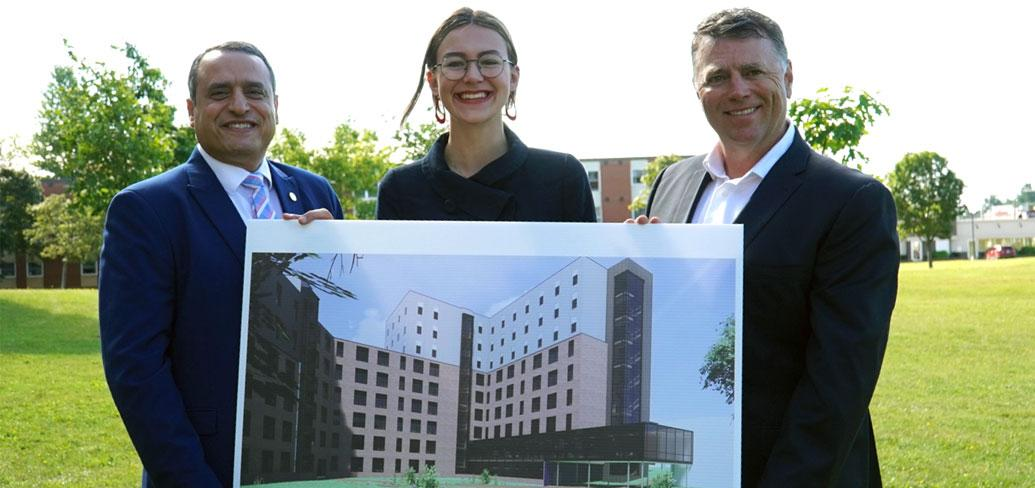 three people holding a picture of a building