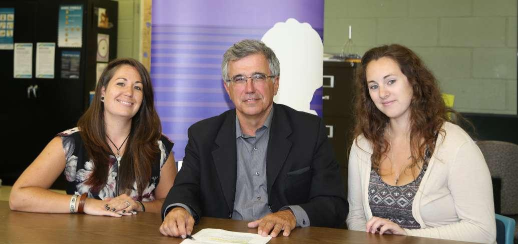 Two women sitting at a table with Minister Richard Brown with purple banner stand in background