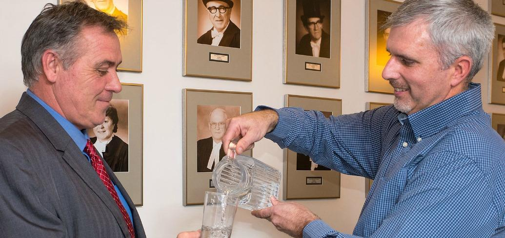 Photo shows Environmental Advisory Council Chair Dean Stewart pouring a glass of water for Communities, Land and Environment Minister Robert Mitchell and