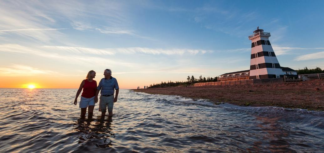 Photo shows a couple strolling on the beach near the West Point Lighthouse.