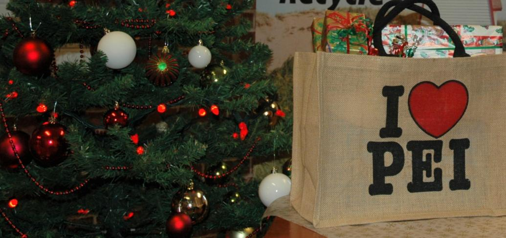 a Christmas tree beside with a shopping bag full of wrapped gifts