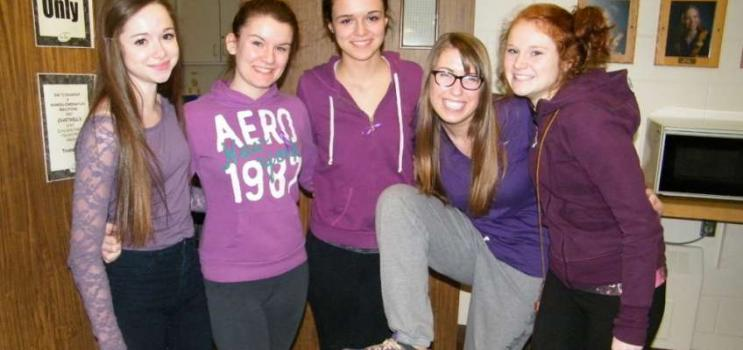 Group of PEI high school students dressed in purple in hallway