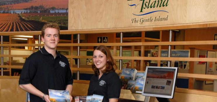Two VIC summer staff hold visitors guides