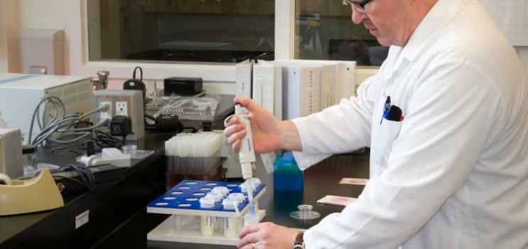 Man wearing white lab coat using laboratory equipment in a lab