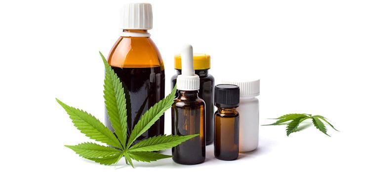 Sur la photo, il y a divers produits de cannabis avec une feuille de cannabis à l'avant-plan et une autre à l'arrière-plan.