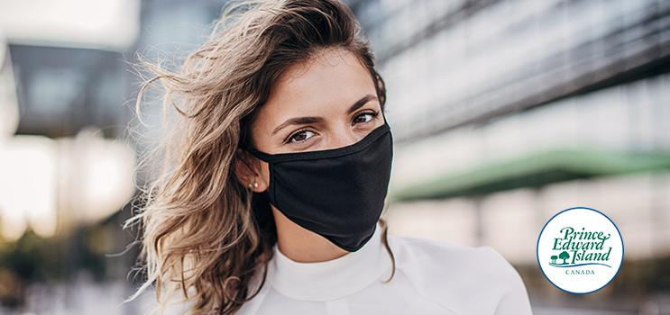 Woman wearing non-medical mask with Government of PEI wordmark in corner of image