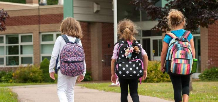 Three elementary school children walking to front door of PEI school