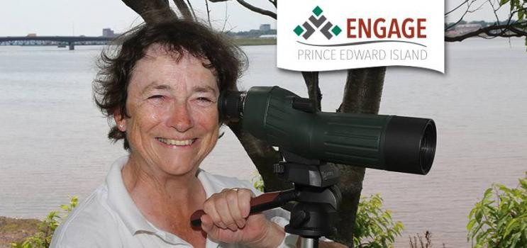 Diane Griffin poses with binoculars on a tripod in front of Hillsborough River