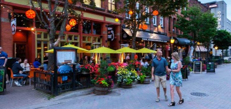 Male and female couple stroll along Victoria Row on a summer evening, PEI