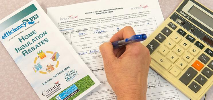 woman completing application for Energy Efficiency Loan program