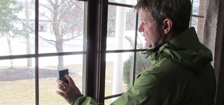 Male home energy inspector takes a reading with a meter at a picture window