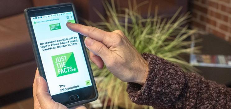 Woman holding mobile photo that is displaying the JUST THE FACTS PEI cannabis website