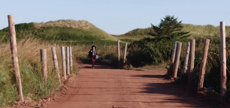 Female walking on red dirt road of Prince Edward Island
