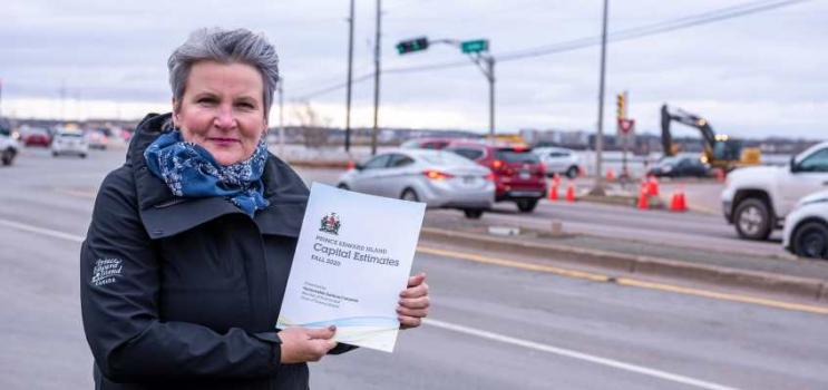 Minister Compton holding a copy of the Capital Budget